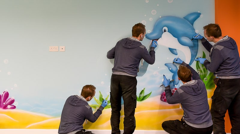dolphin mural painted on the wall by mural artist