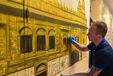 Mural artist painting golden temple mural