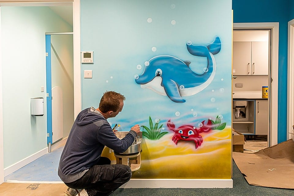 Artist painting dolphin and crab mural on the wall