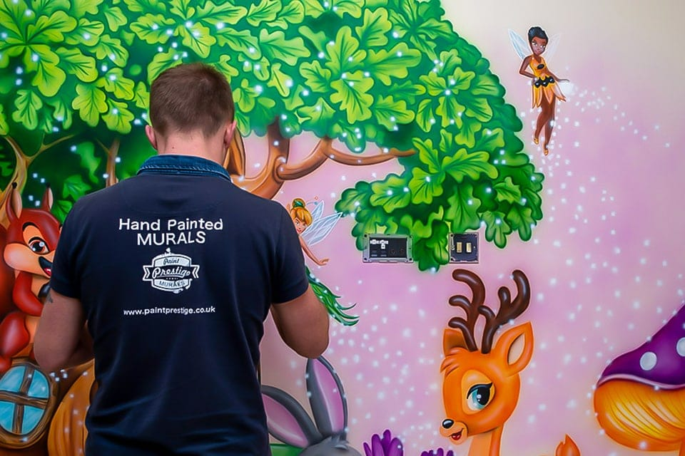 Mural artist painting woodland mural on the wall