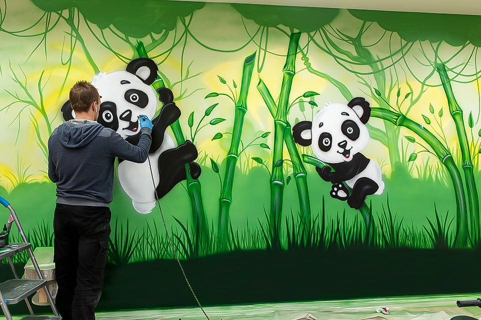 Mural artist painting jungle with pandas mural on the wall