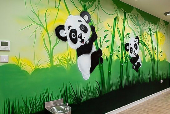 Two beautiful pandas on the bamboo sticks on the jungle wall mural
