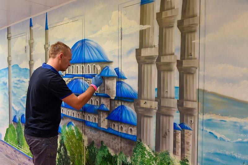Muralist painting blue mosque mural