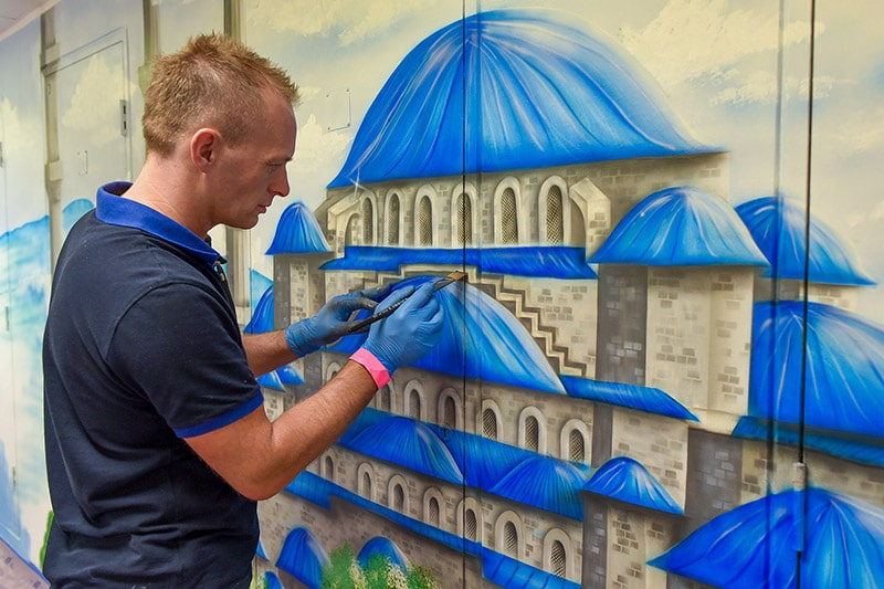 Artist painting blue mosque mural on the wall