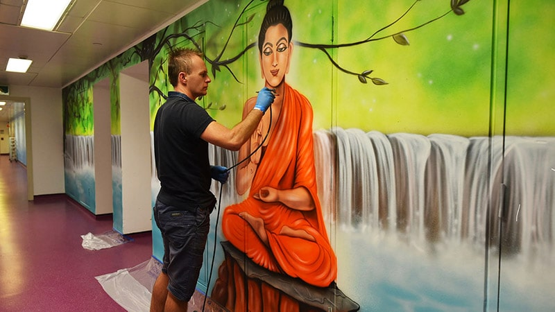 Artist painting Buddha mural on the wall