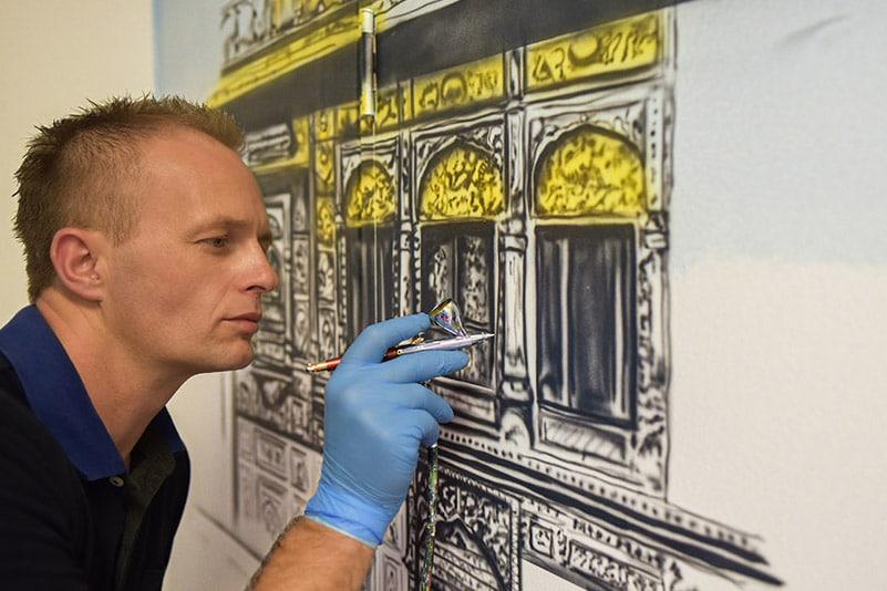 Artist painting golden temple mural